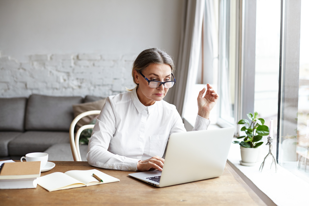 Beautiful,Concentrated,Middle,Aged,Businesswoman,Wearing,Rectangular,Glasses,While,Keyboarding