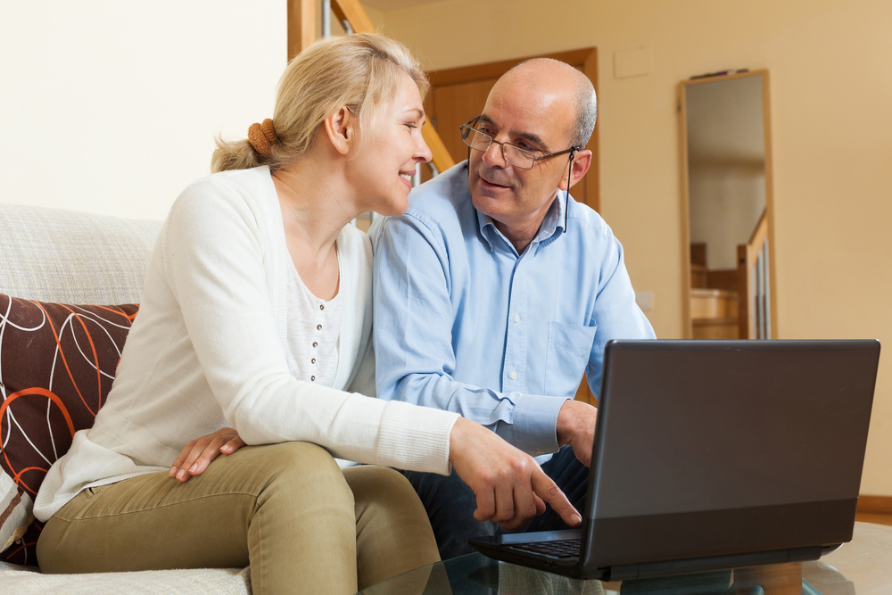 Smiling,Mature,Couple,With,Laptop,At,Table,In,Home