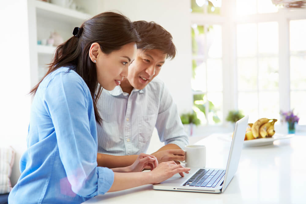 Asian,Couple,Looking,At,Laptop,In,Kitchen