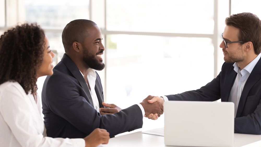 Happy,African,American,Couple,Shake,Hand,Of,Insurer,Salesman,Buy